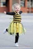 Pequeña muchacha rubia en el traje de la abeja que baila al aire libre Fotografía de archivo libre de regalías
