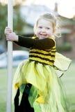 Pequeña muchacha rubia en el traje de la abeja que juega al aire libre Imagen de archivo libre de regalías
