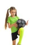 Pequeña muchacha rubia en jugar uniforme del deporte con el balón de fútbol Imágenes de archivo libres de regalías