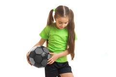 Pequeña muchacha rubia en jugar uniforme del verde con el balón de fútbol Fotos de archivo