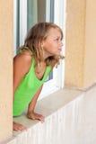 Pequeña muchacha rubia en la ventana, retrato al aire libre Foto de archivo