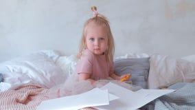 Pequeña muchacha rubia encantadora en el vestido rosado sosteniendo de fieltro-plumas y sentándose en cama entre el papel almacen de video