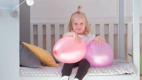 Pequeña muchacha rubia encantadora que se sienta en cama en su sitio con los globos rosados y la sonrisa metrajes