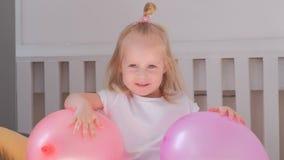 Pequeña muchacha rubia encantadora que se sienta en cama en su sitio con los globos rosados y la sonrisa Retrato almacen de metraje de vídeo