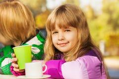 Pequeña muchacha rubia hermosa con la taza verde imagen de archivo
