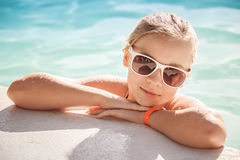 Pequeña muchacha rubia hermosa con las gafas de sol en piscina Fotos de archivo