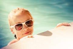 Pequeña muchacha rubia hermosa con las gafas de sol en piscina Fotografía de archivo