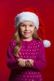 Pequeña muchacha rubia hermosa en el sombrero rojo de Papá Noel que sostiene nieve. foto de archivo