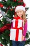 Pequeña muchacha rubia hermosa que lleva a cabo muchos presentes. imagen de archivo