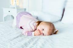 Pequeña muchacha rubia linda en las manos y rodillas en la cama blanca Fotos de archivo libres de regalías
