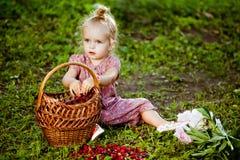 Pequeña muchacha rubia linda en un mono rosado que come las frambuesas franco imagen de archivo