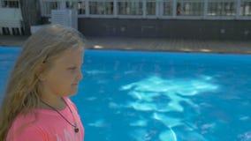 Pequeña muchacha rubia linda que camina a lo largo de una piscina en un día soleado almacen de video