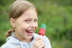 Pequeña muchacha rubia linda que come el helado Fotos de archivo