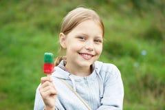 Pequeña muchacha rubia linda que come el helado Fotografía de archivo