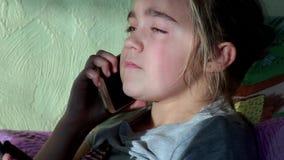 Pequeña muchacha rubia linda que habla en el teléfono móvil que se sienta en el sofá en el apartamento metrajes