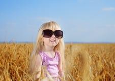 Pequeña muchacha rubia linda que juega en un campo de trigo Foto de archivo libre de regalías