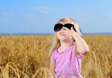 Pequeña muchacha rubia linda que juega en un campo de trigo Imagen de archivo libre de regalías