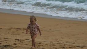 Pequeña muchacha rubia que camina en la playa arenosa almacen de video