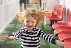 Pequeña muchacha rubia que corre con el pelo azotado por el viento Foto de archivo