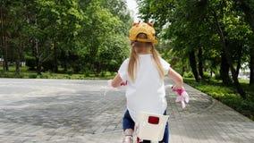 Pequeña muchacha rubia que goza montando su bici al aire libre metrajes