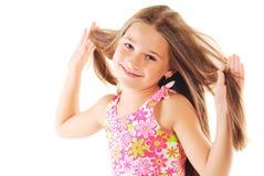 Pequeña muchacha rubia que juega con su pelo Fotografía de archivo