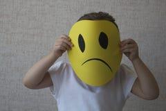 Pequeña muchacha rubia que lleva a cabo las mascarillas tristes que simbolizan emociones cambiantes Foto de archivo libre de regalías