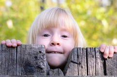Pequeña muchacha rubia que mira a escondidas sobre una cerca de madera imagenes de archivo