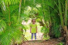 Pequeña muchacha rubia que permanece entre las palmeras al aire libre Fotografía de archivo libre de regalías