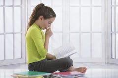 Pequeña muchacha rubia que se sienta en el piso cerca de los libros Imagenes de archivo