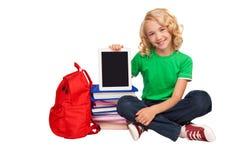 Pequeña muchacha rubia que se sienta en el piso cerca de los libros y de bolso Fotografía de archivo
