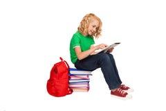 Pequeña muchacha rubia que se sienta en el piso cerca de los libros y de bolso Foto de archivo