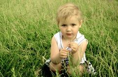 Pequeña muchacha rubia que se sienta en la hierba verde Fotografía de archivo