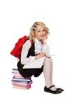 Pequeña muchacha rubia que se sienta en los libros con el libro de texto y vagos rojos Imágenes de archivo libres de regalías