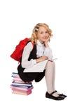 Pequeña muchacha rubia que se sienta en los libros que sostienen el libro de texto Imagen de archivo