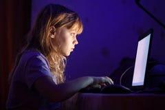 Pequeña muchacha rubia que trabaja en el ordenador portátil en oscuridad Foto de archivo libre de regalías