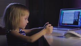 Pequeña muchacha rubia que trabaja en el ordenador portátil en sitio oscuro en la noche almacen de metraje de vídeo