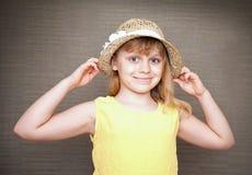 Pequeña muchacha rubia sonriente con el sombrero de paja Foto de archivo libre de regalías