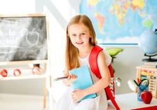 Pequeña muchacha rubia sonriente que se coloca en la sala de clase de la escuela Imágenes de archivo libres de regalías