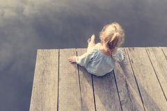 Pequeña muchacha sola que se sienta cerca del río Aventurado situación Imagen de archivo
