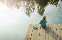 Pequeña muchacha sola que se sienta cerca del río Aventurado situación Fotografía de archivo