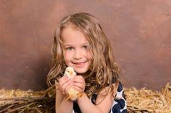 Pequeña muchacha sonriente agradable que abraza el pollo vivo foto de archivo libre de regalías