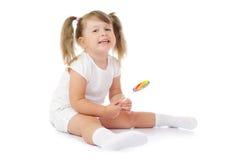 Pequeña muchacha sonriente con el lollipop foto de archivo