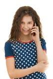 Pequeña muchacha sonriente con el teléfono Imágenes de archivo libres de regalías
