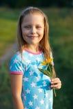 Pequeña muchacha sonriente con la flor amarilla Imagen de archivo