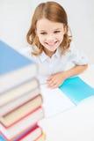 Pequeña muchacha sonriente del estudiante con muchos libros Imágenes de archivo libres de regalías