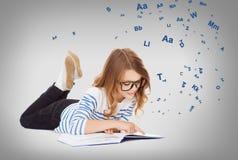 Pequeña muchacha sonriente del estudiante que miente en el piso Fotografía de archivo libre de regalías