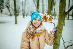 Pequeña muchacha sonriente en casquillo azul en nieve foto de archivo libre de regalías