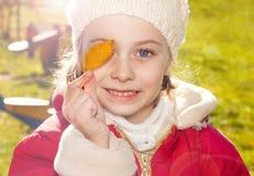 Pequeña muchacha sonriente feliz que sostiene una hoja al aire libre durante otoño Imagen de archivo