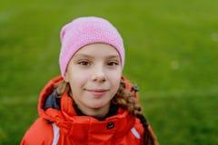 Pequeña muchacha sonriente hermosa en chaqueta roja Fotografía de archivo libre de regalías
