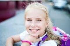 Pequeña muchacha sonriente hermosa en una calle de la ciudad del fondo Foto de archivo libre de regalías